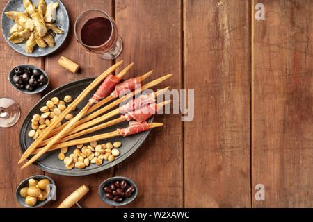 Italian antipasti. Grissini breadsticks with parma ham and roasted almonds, with olives and artichokes, shot from the top on a dark wooden background - Stock Image