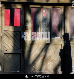 shadow of man falls on to wooden building with red  interior seen through windows - Stock Image