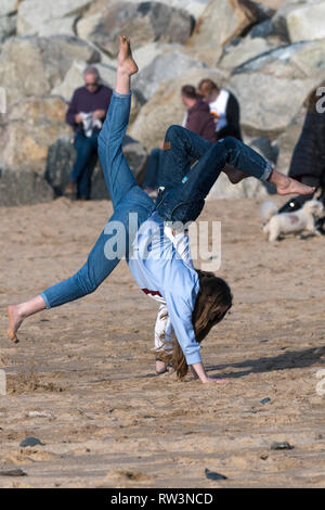 Young energetic teenage girls doing handstands on Fistral Beach in Newquay Cornwall. - Stock Image