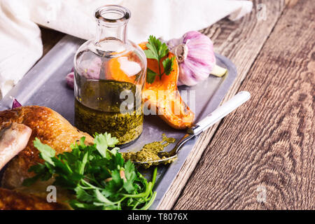 Pesto sauce, roasted chicken legs, pumpkin,  and fresh parsley on rustic wooden table, meat and vegetables roast dinner - Stock Image