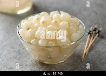 Glass bowl with traditional pickled silverskin onions close up - Stock Image