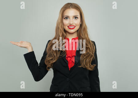 Cheerful woman with empty open hand looking at camera and smiling - Stock Image