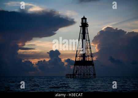 The iron skeletal tower of historic Alligator Reef Light is framed under the anvil of a summer thunderstorm at dawn. - Stock Image