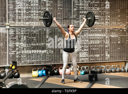 Young athletic woman doing the snatch in a gym raising a barbell weight from floor to above her head in standing posture in a single movement with tra - Stock Image