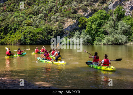 Canoe Kayak. Young people paddling hard the kayak near the cliff on river Nestos in Greece. - Stock Image