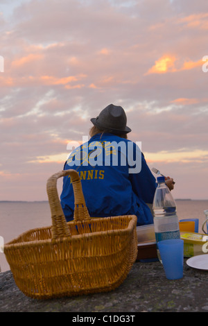 Two teenagers having an evening picnic by the sea in the Archipelago of Stockholm, Sweden. - Stock Image
