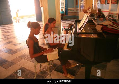 Cuba Trinidad Young girls practicing classical piano in Casa Fischer Photo CUBA1462 Copyright Christopher P Baker - Stock Image