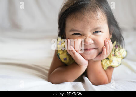 healthy cute little asian girl toddler smiling on bed. concept of happiness, childhood and lifestyle - Stock Image