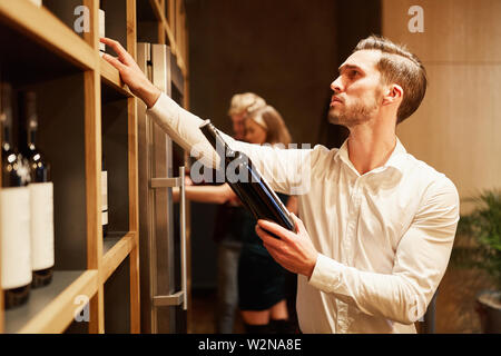 Young man as a wine connoisseur choosing red wine on the shelf in the wine shop - Stock Image
