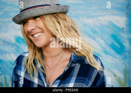 Portrait of smiling woman with long blond hair wearing blue checkered shirt and grey Trilby hat. - Stock Image