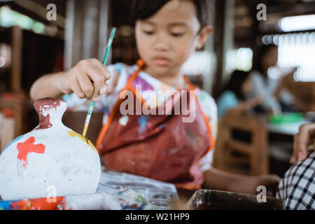 daughter learning about painting color in pottery workshop - Stock Image