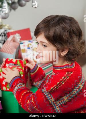 Boy Stacking Christmas Gifts - Stock Image