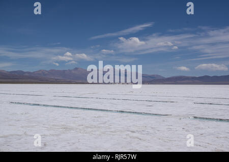 Salinas grandes and salt mining area in northern Argentina, Jujuy region on a sunny day with mountains in the background - Stock Image