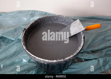 Decorative cement plaster and a trowel in a construction bucket ready for plastering - Stock Image