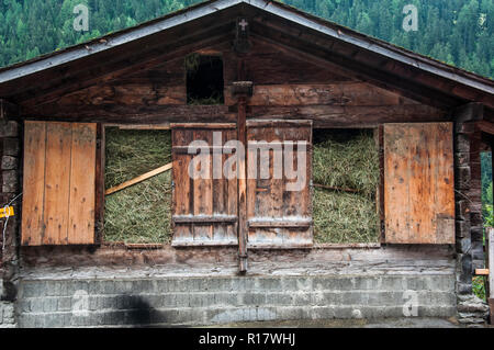 Traditional barn packed with fresh-cut fodder in the Loetschental Valley, Valais, Switzerland - Stock Image