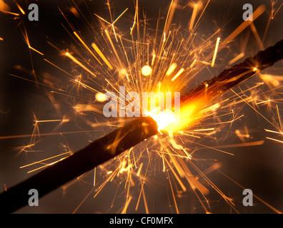 A burning sparkler firework close-up spitting sparks - Stock Image