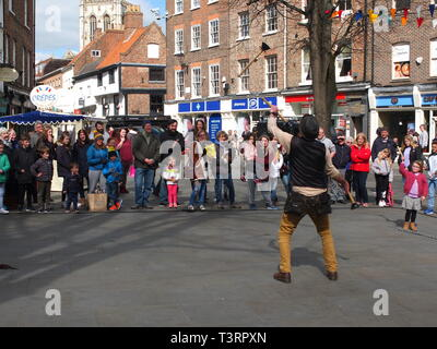 Street performer juggling sink plungers watched by crowd in King's Square,York,UK with York Minster in background - Stock Image
