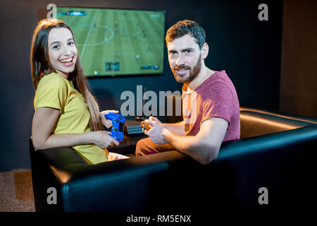 Portrait of a happy man and woman with joy sticks playing football with gaming console sitting on the couch at the playing club - Stock Image