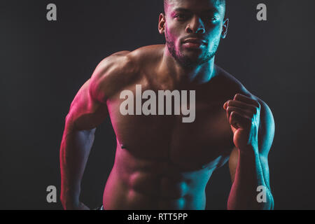 Close shot of athletic African well built man with six pack abs posing shirtless at studio over dark background. - Stock Image