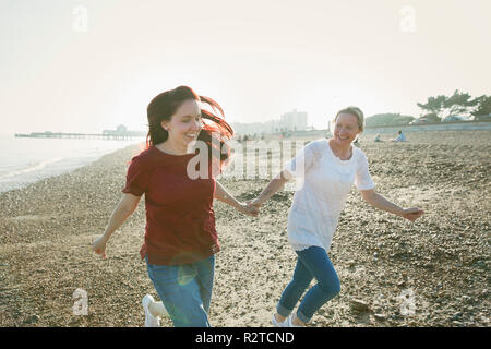 Playful, affectionate lesbian couple holding hands and running on sunny beach - Stock Image
