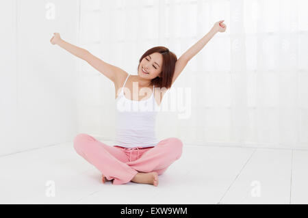 Young woman sitting on the floor with arms outstretched, - Stock Image