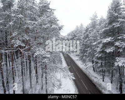 Aerial top view of road in winter forest - Stock Image
