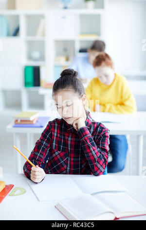 Pensive little girl with crayon sitting by desk in classroom and looking at blank page of copybook while drawing - Stock Image
