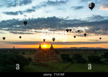 Early morning bright golden sun silhouettes hot air balloons and ancient pagodas and temples of Bagan, Myanmar. - Stock Image