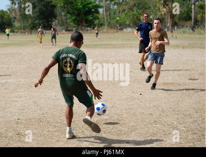 Hospital Corpsman 1st Class Joshua Maestas, from Kelseyville, California, assigned to Commander, U.S. 7th Fleet, and members of the Timor-Leste Defense Force and the National Police of Timor-Leste play soccer following the closing ceremony of CARAT Timor-Leste 2018 at Hera Naval Base, Aug. 30, 2018. CARAT Timor-Leste 2018 is designed to address shared maritime security concerns, build relationships and enhance interoperability among participating forces. (U.S. Navy photo by Mass Communication Specialist 3rd Class Danny Ray Nuñez Jr./Released) - Stock Image