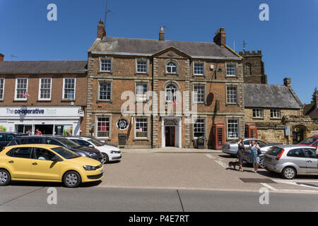 The market square in the historic market town of Towcester, Northamptonshire, UK; the 18th century building to the rear houses the Post Office. - Stock Image