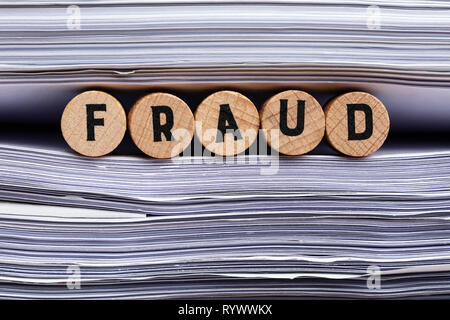 Wooden Cork With Fraud Text Between Stacked Paper - Stock Image