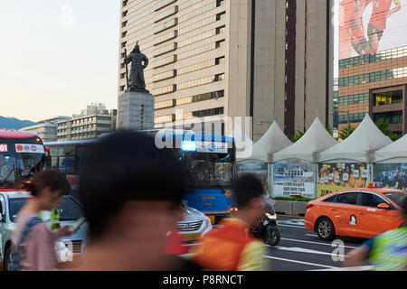 Statue of Admiral Yi Sun-Shin in Gwanghwamun, Seoul, South Korea, with motion blurred pedestrians crossing the street in the foreground. - Stock Image