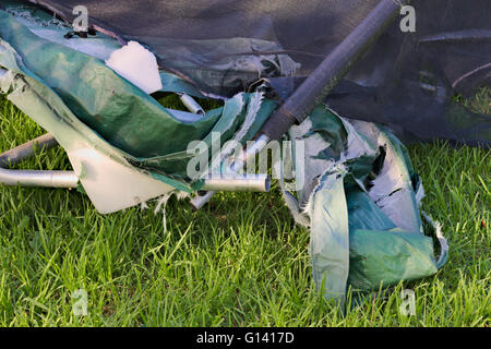Detailed parts of a damaged trampoline on a grassy background. - Stock Image