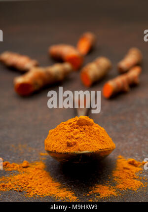 turmeric powder in an old vintage spoon, turmeric roots on a dark background - Stock Image