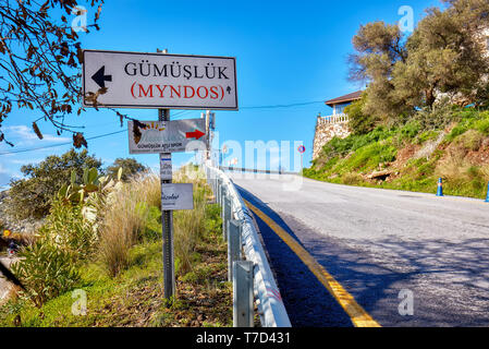Bodrum, Turkey - January, 2019: Road sign of touristic Gumusluk Myndos town in Bodrum, Mugla, Turkey. Editorial. - Stock Image
