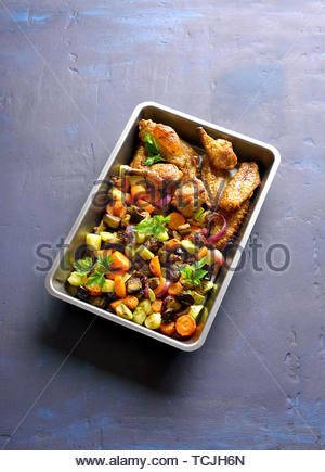 Oven baked vegetables and chicken wings in baking tray on blue stone background - Stock Image