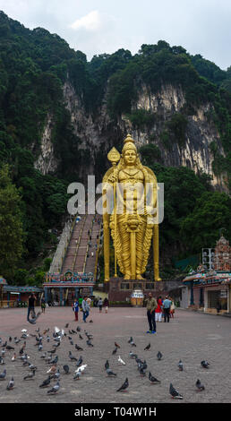The huge golden Murugan statue stands at the entrance stair way to Batu Caves, Kuala Lumpur, Malaysia. - Stock Image