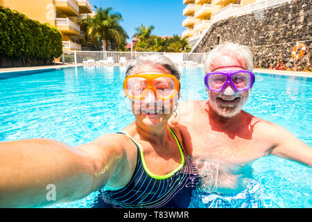 Happy cheerful people old senior man and woman have fun together in the summer swimming pool activity taking selfie pictures with scuba masks on the f - Stock Image