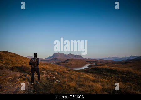 A lone walker views Benn Airigh Charr and Loch Kernsary in the evening light, Poolewe, Scotland. - Stock Image