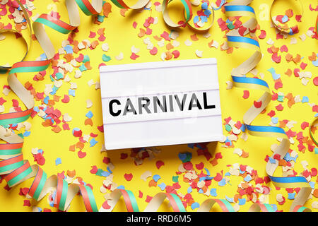 carnival flat lay with text on light box sign confetti and streamers - Stock Image