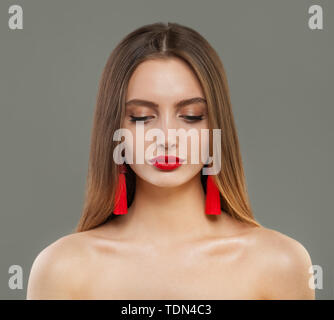 Beautiful fashion model woman with red jewelry earrings portrait - Stock Image