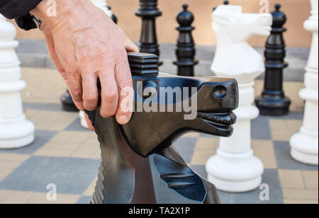 man moving giant chess piece horse outdoor on the city street. hands closeup - Stock Image