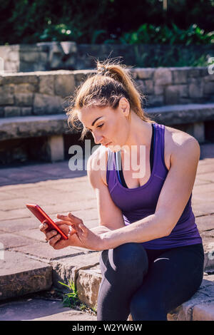 young sporty woman sitting looking at the phone at park, technology at sports and healthy lifestyle - Stock Image