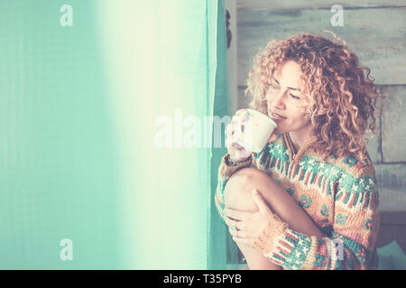 Happy quiet and peaceful young attractive woman enjoy the relax time at home drinking a cup of tea and looking outside the window - curly hair for cau - Stock Image