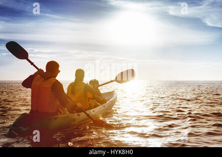 Family of father mother and son kayaking at sea sunset - Stock Image