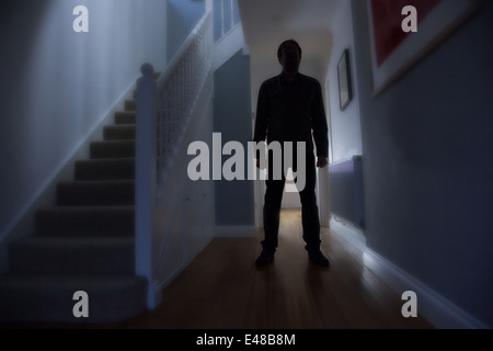 Silhouette of a man standing in a hallway of a house with the stairs to his right. - Stock Image