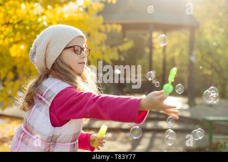 Autumn portrait of a child girl with soap bubbles, background yellow autumn trees, sunset. - Stock Image