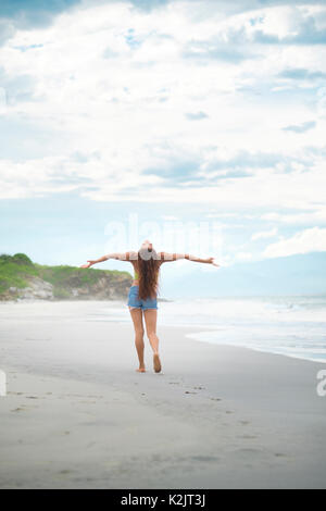 Woman raises arms and face in happiness toward the sky - Stock Image