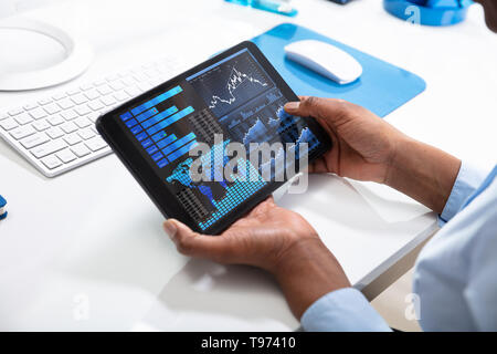 Businessperson's Hand Pointing On Tablet Screen Showing Graph Over The Desk - Stock Image