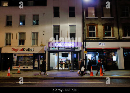 People walking past shops at night on Tottenham Court Road, London, England, UK - Stock Image